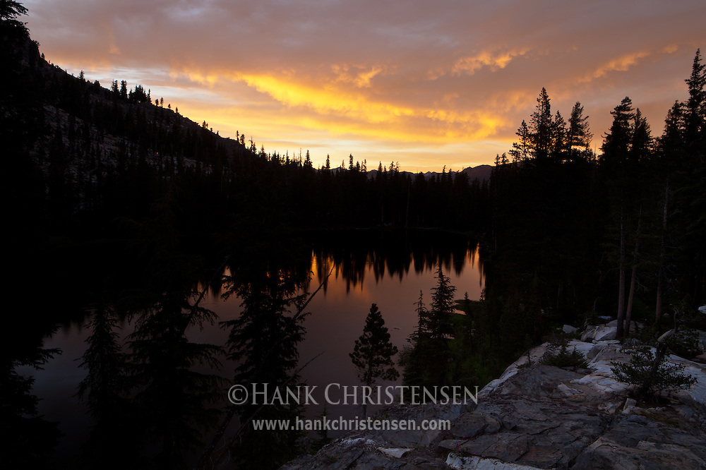 The dramatic skies of sunset are reflected in one of lakes of the Ten Lakes chain, Yosemite National Park