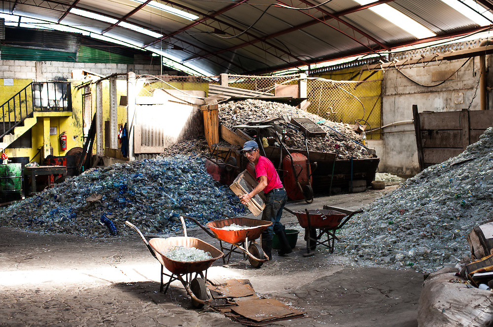 A worker at the glassblowing collective Copavic in Cantel, Guatemala gathers shards of used bottles to turn into glassware.