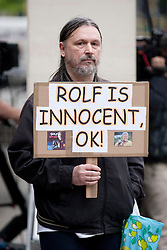 © Licensed to London News Pictures. 23/09/2013. London, UK. A lone man with a placard declaring artist and television celebrity Rolf Harris to be innocent is seen outside Westminster Magistrates Court in London today (23/09/2013). Harris, 83, has been charged with nine counts of indecent assault and four counts of making indecent images of a child. The alleged indecent assaults date from 1980 to 1986 and relate to two complainants aged 14 and 15 at the timePhoto credit: Matt Cetti-Roberts/LNP