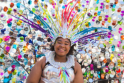 London, August 27 2017. A girl's glittering headdress catches the light as Family Day of the Notting Hill Carnival gets underway. The Notting Hill Carnival is Europe's biggest street party held over two days of the bank holiday weekend, attracting over a million people. © Paul Davey.