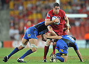 "James Horwill charges upfield into the tackles of Nathan Sharp (left) and James Stannard (right) during the Super 15 Rugby Union match (Round 2) between the Queensland Reds and Western Force played at Suncorp Stadium (Brisbane, Australia) on Saturday 3rd March 2012 ~ Queensland (35) defeated the Western Force (20) ~ This image is intended for Editorial use only - Required Images Credit ""Steven Hight - Aura Images"""
