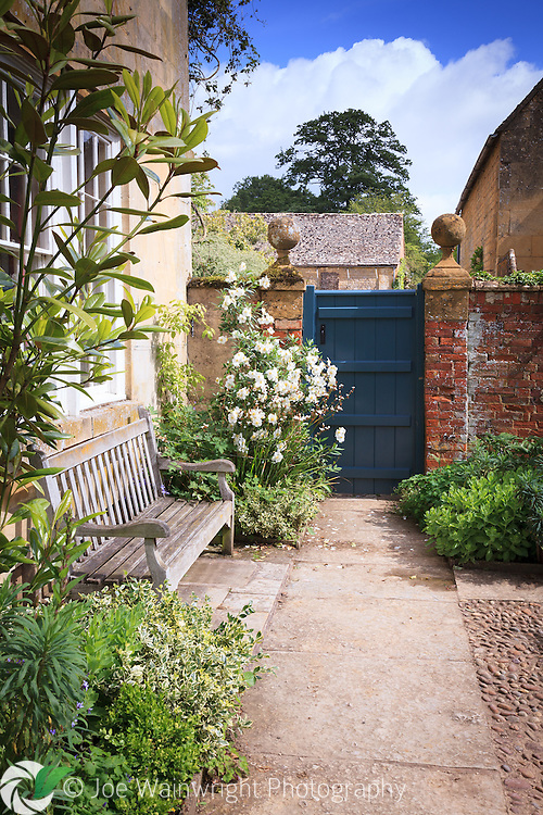 Plants, including euonymus and sedum spill over a pathway at Hidcote Manor Gardens, Gloucestershire.