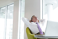 Relaxed mature businessman reclining at lobby