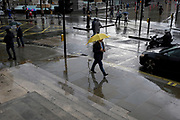 A pedestrian carrying a yellow umbrells walks in the last drops of rain after an autumnal downpour in Trafalgar Square in central London, on 1st October 2019, in London, England.