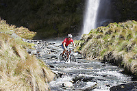 Cyclist riding in river with waterfall