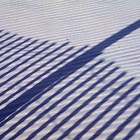 The shadow of a dune fence is cast across the sand in Chincoteague, VA.