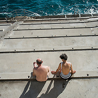 A older couple bath in the sun overlooking the Mediterranean Sea in Monte Carlo, Monaco.