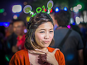 "31 DECEMBER 2012 - BANGKOK, THAILAND:  A Thai television reporter wears a 2013 hat during her ""stand up"" report at the New Year's Eve party and countdown in Ratchaprasong Intersection in Bangkok. The traditional Thai New Year is based on the lunar calender and is celebrated in April, but the Gregorian New Year is celebrated throughout the Kingdom, especially in larger cities and tourist centers, like Bangkok, Chiang Mai and Phuket. The Bangkok Countdown 2013 event was called ?Happiness is all Around @ Ratchaprasong.? All of the streets leading to Ratchaprasong Intersection were closed and the malls in the area stayed open throughout the evening.  PHOTO BY JACK KURTZ"