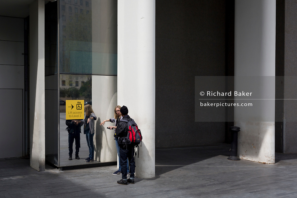 Two women talk outside the rear Artists' Entrance of the Royal Festival Hall on the Southbank, on 2nd May 2019, in London, England.