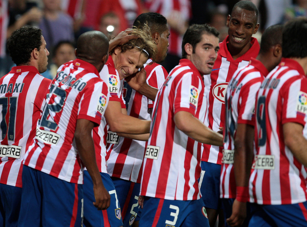 Atletico Madrid's Diego Forlan of Urugay, center, celebrates after scoring against Almeria's with fellow team members Antonio Lopez, Maxi Rodriguez of Argentina, left, Paulo Assuncao of Brazil during their Spanish La Liga soccer match at the Vicente Calderon stadium in Madrid, Wednesday, Sept. 23, 2009.