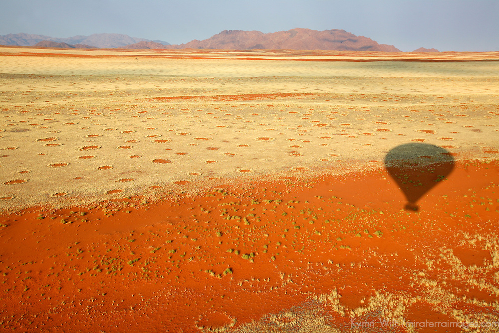 Africa, Namibia, Sossusvlei. Hot air ballooning over the red dunes, grasses, and landscape of the NamibRand Nature Reserve.