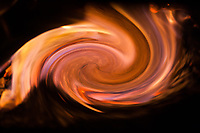 abstract fire storm in whirpool shape with shades of red and yellow on black background
