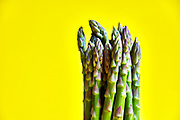 bunch of fresh and healthy asparagus standing with yellow background