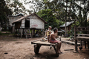 Father and son on a wooden cart outside their home in Kbal Romeas. Their house, like many others, has been spray-painted in red with the sign LSS2 (Lower Sesan 2) meaning they have to be relocated into the designated area, a scorching dusty piece of land along the main road to Ratanakiri province, northern Cambodia. Their village will soon be flooded by the reservoir of the new $800 million dam being built a few kilometers downstream.