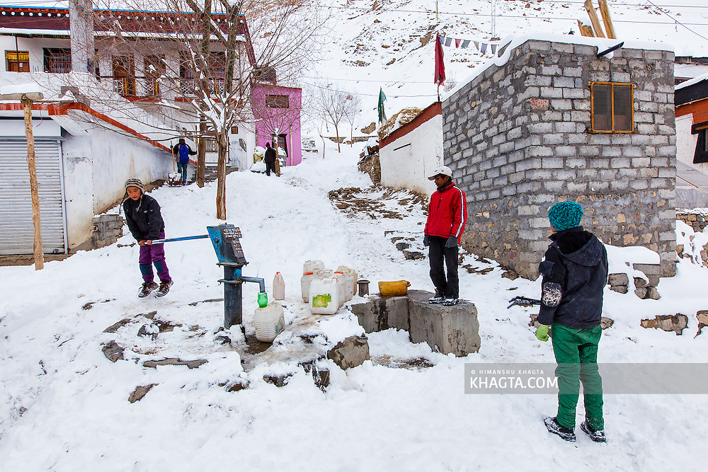 Spiti children waiting for their turn to fetch water from the handpump in Kaza village, the only source of water in a Spiti winter. The handpump is covered after 3pm everyday to prevent it from freezing.