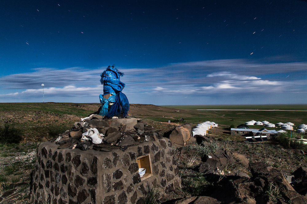 An ovoo, a sacred offering to the spirits or spiritual often found on roads or trails, sits on top of a hill overlooking the Three Camel Lodge in the Gobi Desert of Mongolia on August 1, 2012. © 2012 Tom Turner Photography