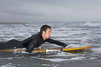 Surfer puddling on surfboard in water side view