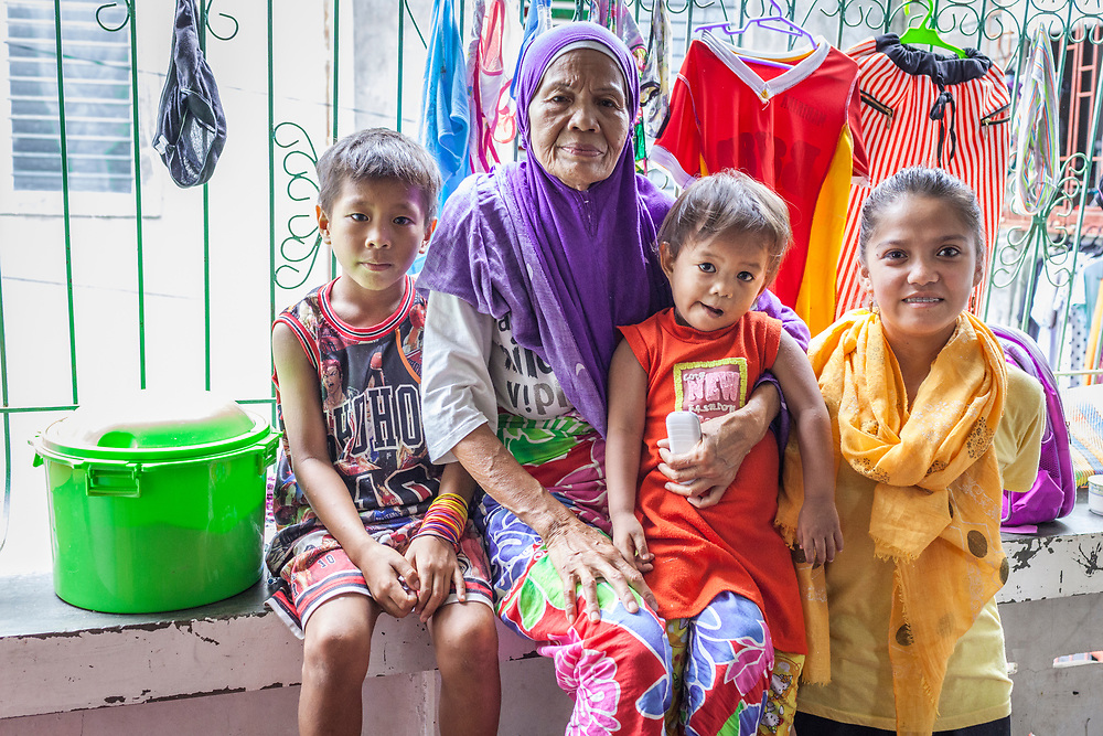 Davao City, Mindanao, Philippines - JUNE 22: A portrait of Casana Calandada and her family members.  Casana walked for 6 hours to the nearest city to escape the ongoing conflict after the ISIS backed Maute Group has sieged the city. Casana and 5 other family members found refuge in a house that she shared with 35 other people in the Mini Forest Barangay 23C. Currently, over 570 families and roughly 2500 evacuees from Marawi reside in the area.