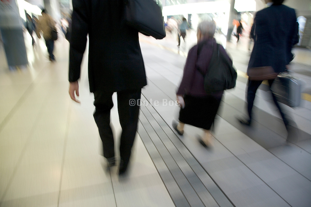 a small elderly woman being passed in a hurry by two young corporate employees