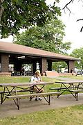 Man age 22 taking an early morning break. Dragon Festival Lake Phalen Park St Paul Minnesota USA