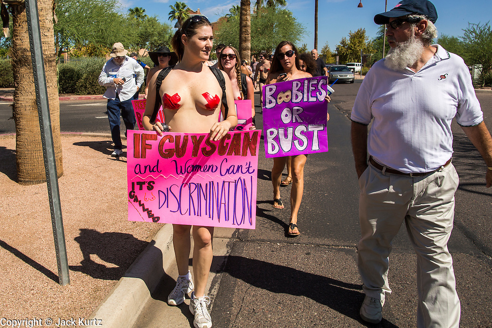 26 MARCH 2012 - PHOENIX, AZ: KELLY CAYE, a topless protester, talks a male spectator during a topless protest in Phoenix. About 40 people marched through central Phoenix Sunday to call for a constitutional amendment to give women the same right to go shirtless in public that men have. The Phoenix demonstration was a part of a national Topless Day of Protest. Phoenix prohibits women from going topless in public so protesters, women and men, covered their nipples and areolas with tape. The men did it to show solidarity with the women marchers.    PHOTO BY JACK KURTZ