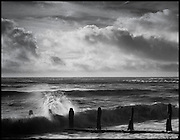 Waves break against teh groynes on Winchelsea beach, east Sussex. Taken on Pentax 67 with Rollei Superpan 200.