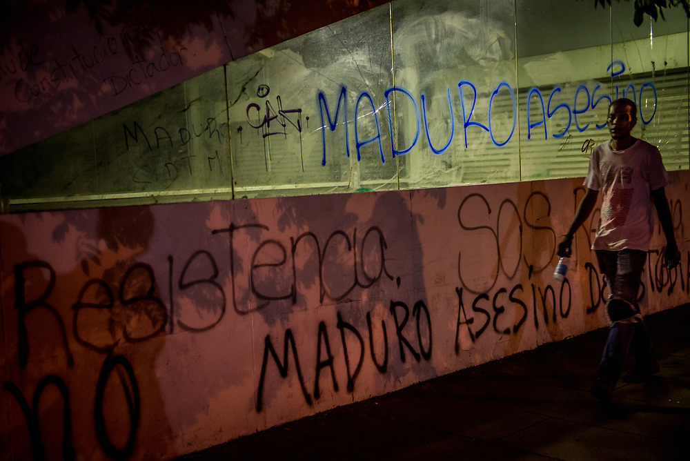 """CARACAS, VENEZUELA - MAY 20, 2017:  A man walks past street graffiti that says """"SOS"""" and """"Assassin Maduro"""". The streets of Caracas and other cities across Venezuela have been filled with tens of thousands of demonstrators for nearly 100 days of massive protests, held sincde April 1st. Protesters are enraged at the government for becoming an increasingly repressive, authoritarian regime that has delayed elections, used armed government loyalist to threaten dissidents, called for the Constitution to be re-written to favor them, jailed and tortured protesters and members of the political opposition, and whose corruption and failed economic policy has caused the current economic crisis that has led to widespread food and medicine shortages across the country.  Independent local media report nearly 100 people have been killed during protests and protest-related riots and looting.  The government currently only officially reports 75 deaths.  Over 2,000 people have been injured, and over 3,000 protesters have been detained by authorities.  PHOTO: Meridith Kohut"""