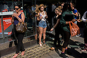 A woman with blowing hair wearing cut-off denim shorts with other shoppers outside a sunglasses shop window selling Ray Bans on Long Acre in London's Covent Garden.