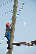 Woman at the College of Southern Idaho Challenge Rope Course with the moon beyond in Twin Falls, Idaho.