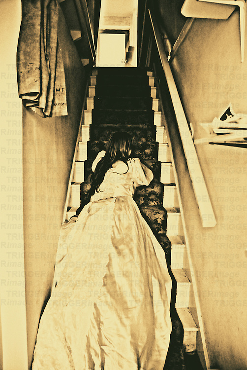 A young woman in a long silk dress lying on stairs