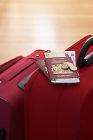 Two suitcases with passports on them standing in hallway elevated view close up
