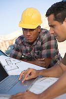 Architect and construction worker using laptop on construction site