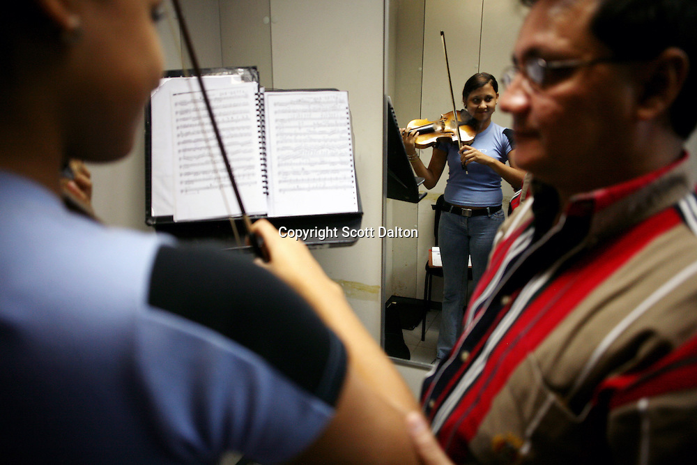 A young girl receives one on one instruction for the violin in a practice room at the Montealban music center in Caracas on November 10, 2006. The Venezuelan government sponsors the National System of Youth and Children's Orchestras of Venezuela, which provides instruments and music training to the countries youths. The program was founded 31 years ago and has over 250,000 children participating throughout the country. (Photo/Scott Dalton)