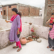 CAPTION: Megha Burvey, a TARU consultant, measures the difference in surface temperatures between cool and untreated roofs. LOCATION: . INDIVIDUAL(S) PHOTOGRAPHED: Megha Burvey, Arya and Mamta Chouhan.