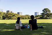 Couple is seating on the grass in Imperial West Garden  - Tokyo - Japan - 2018 August 26th