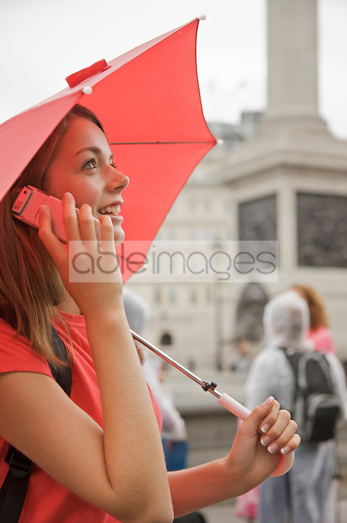 Teenaged girl holding a red umbrella and talking on a cell phone in London Trafalgar Square