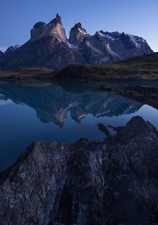 Hones of Paine twilight reflect in the calm waters of Lago Nordenerskjold, Torres del Paine National Park, Chile