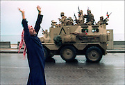 (FILES) A Kuwaiti citizen raises his arms in celebration as a Saudi personnel carrier passes on the street 27 February 1991 after allied forces rolled into Kuwait City 27 February 1991.