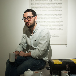 London, UK - 29 January 2014: artist Simon Fujiwara has a coffee break while setting up his installation at the Contemporary Art Society until 29 March.