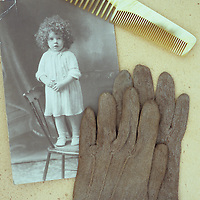 Pair of pale brown cotton Victorian childs gloves lying on black and white studio photo of young child next to bone comb