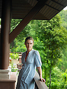 Young Woman Beneath Veranda with Glass of Water