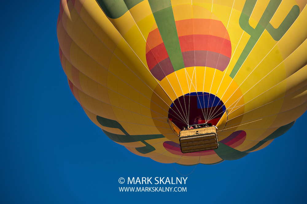 Looking up at a colorful hot air balloon just after lift off.  Set against a deep blue sky.