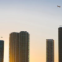Passenger aircrafts flying over skyscrapers at sunset, MIami, Florida, USA