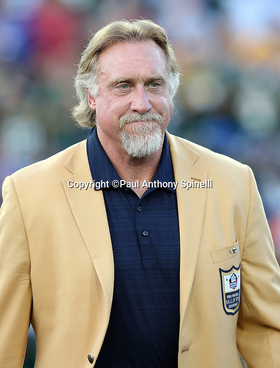 Former NFL player and Green Bay Packers linebacker coach Kevin Greene smiles while being announced over the public address system as he walks onto the field as a new member of the Pro Football Hall of Fame before the 2016 NFL Pro Football Hall of Fame preseason football game against the Indianapolis Colts on Sunday, Aug. 7, 2016 in Canton, Ohio. The game was canceled for player safety reasons due to the condition of the paint on the turf field. (©Paul Anthony Spinelli)