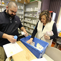 Trea Wyatt, a pharmacy technician, and Barbara Lindsey, a pharmacy volunteer, at the Tree of Life Clinic, work on stocking the shelves before the opening of the clinic on Wednesday night in Tupelo.