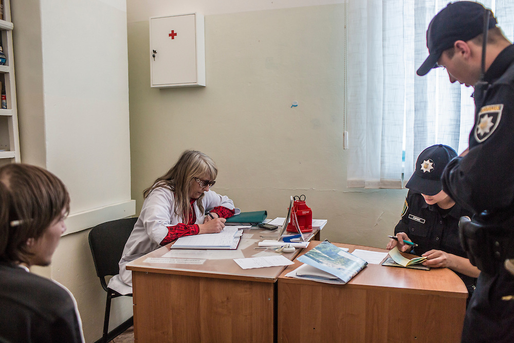 LVIV, UKRAINE - SEPTEMBER 16, 2015: Members of the new Lviv police, including Tetiana Soroka, 25, second from right, fill out paperwork connected to a routine medical exam for Vladimir, 26, after arresting him when he was found intoxicated and sleeping in the city's central square and then swore at police officers in Lviv, Ukraine. In an effort to reform the notoriously corrupt Ukrainian police force, an entirely new force has been established in several cities, including Kiev and Lviv, with a primary focus on patrolling the streets. CREDIT: Brendan Hoffman for The New York Times