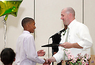 Keivon Greene receives a certificate of completion from Principal Aaron Smith during the 8th grade recognition ceremony at Cleveland PK-8 School in Dayton, May 25, 2012.