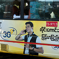 Myanmar (Burma). Yangon. Public bus painted with an advert for a mobile phone.