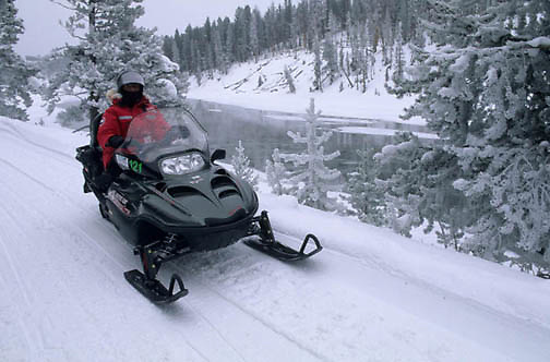 Yellowstone National Park, Snowmobiling in park along Yellowstone River using less polluting 4 stroke sled.