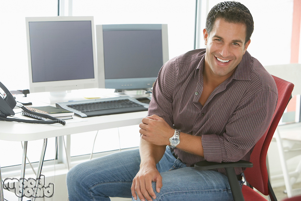 Businessman smiling by computers in office portrait